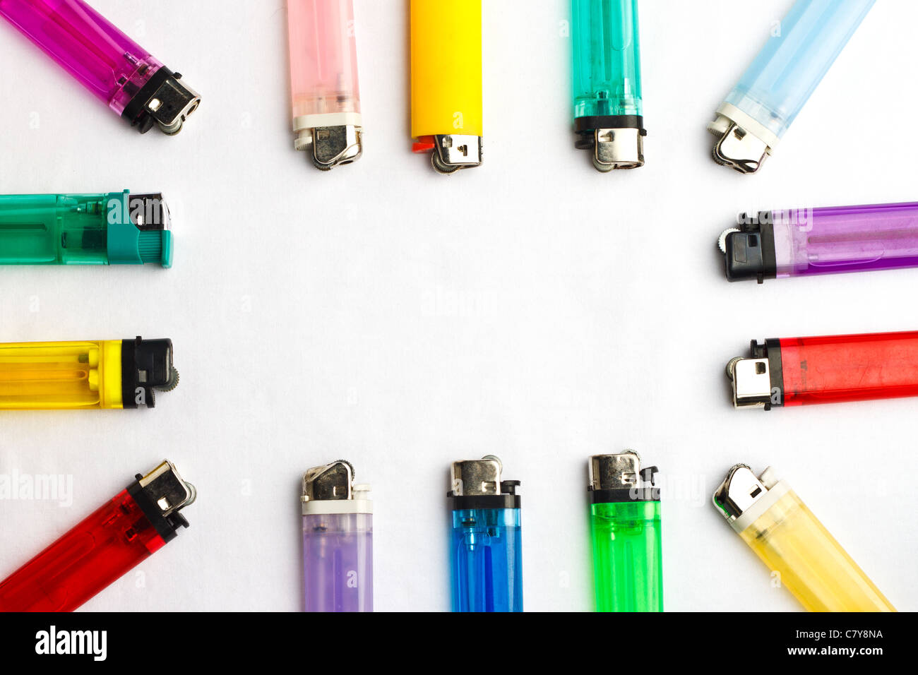 Colorful assortment of disposable lighters bordering a white background - Stock Image