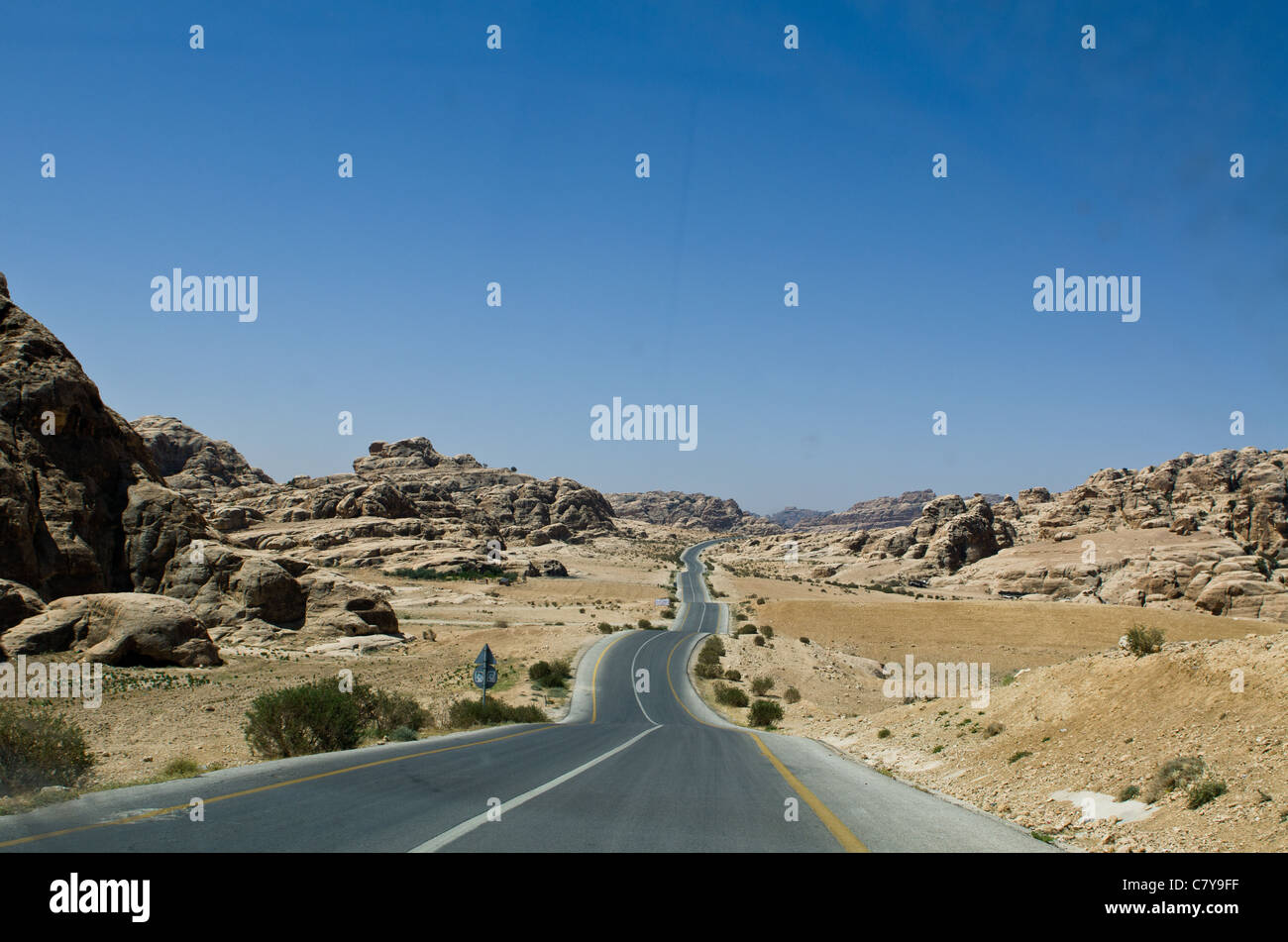 the road leading from little petra to petra in the Jordanian Desert, scattered around are remnants of carved dwellings - Stock Image