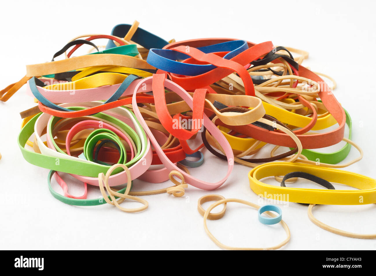 Assortment of rubber bands piled against white background - Stock Image