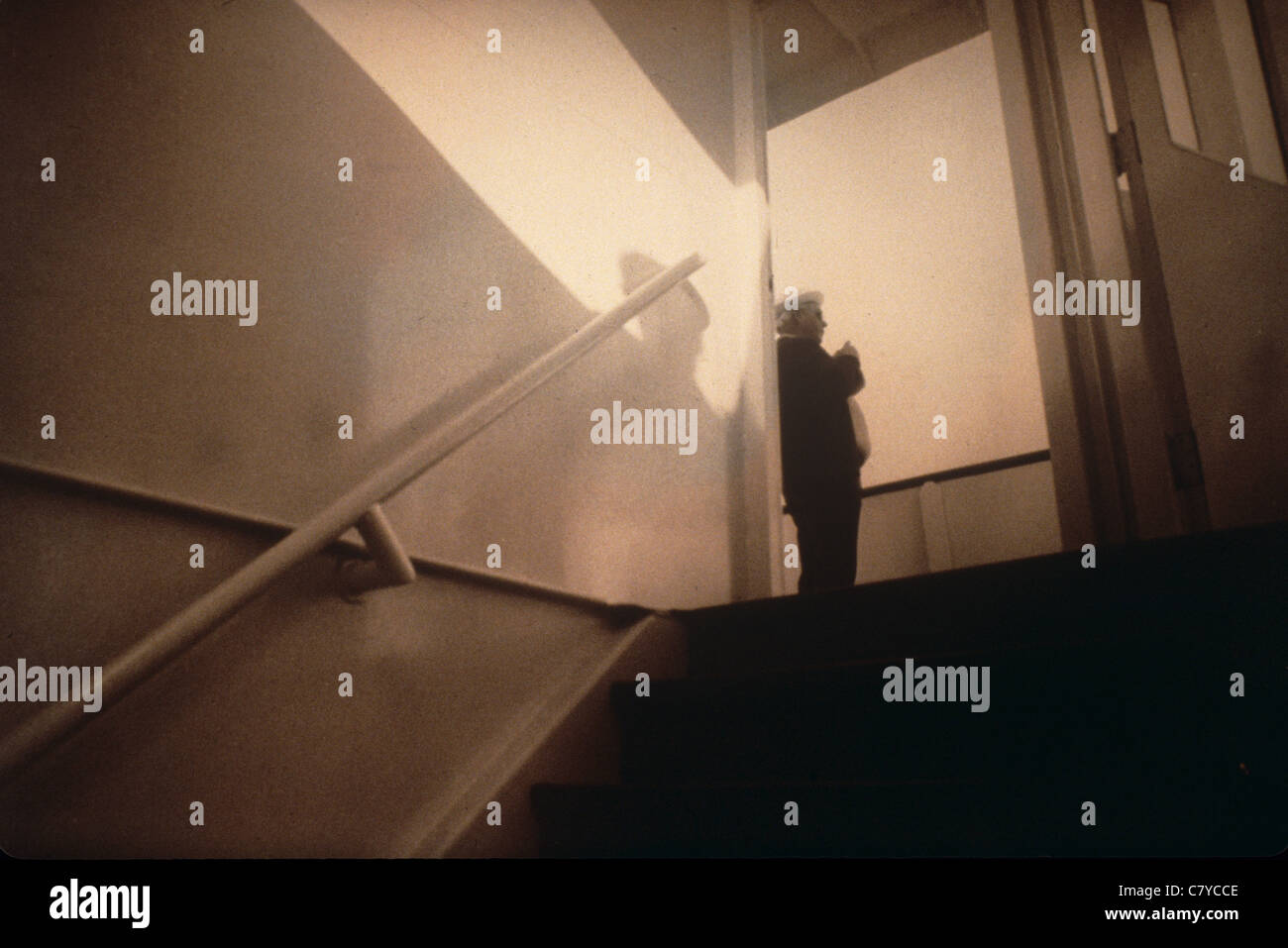 man at top of stairs with wall shadow - Stock Image