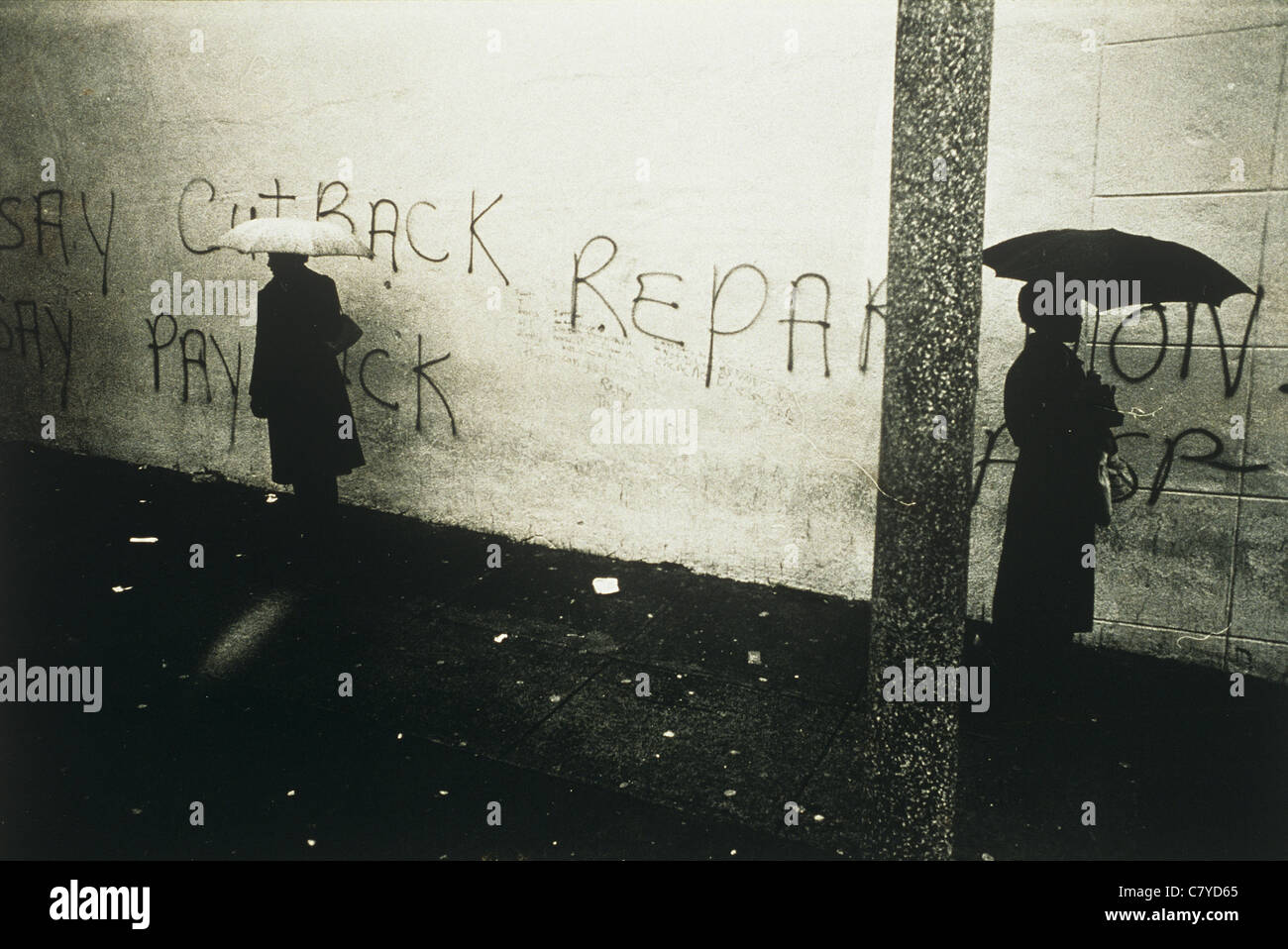 Two women walking in opposite directions with umbrellas against wall with writing - Stock Image
