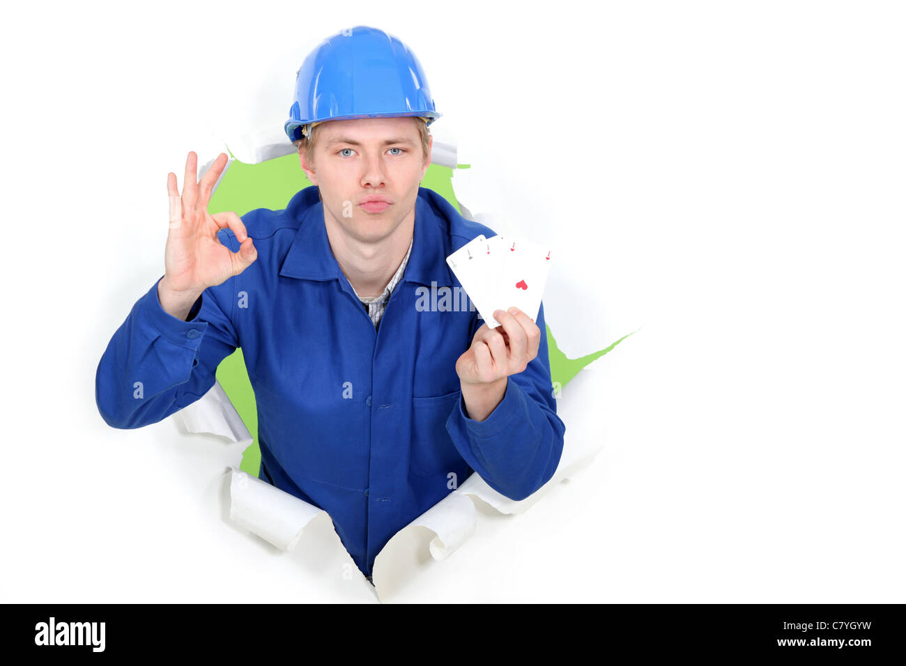 Tradesman giving the a-ok sign and holding up cards - Stock Image