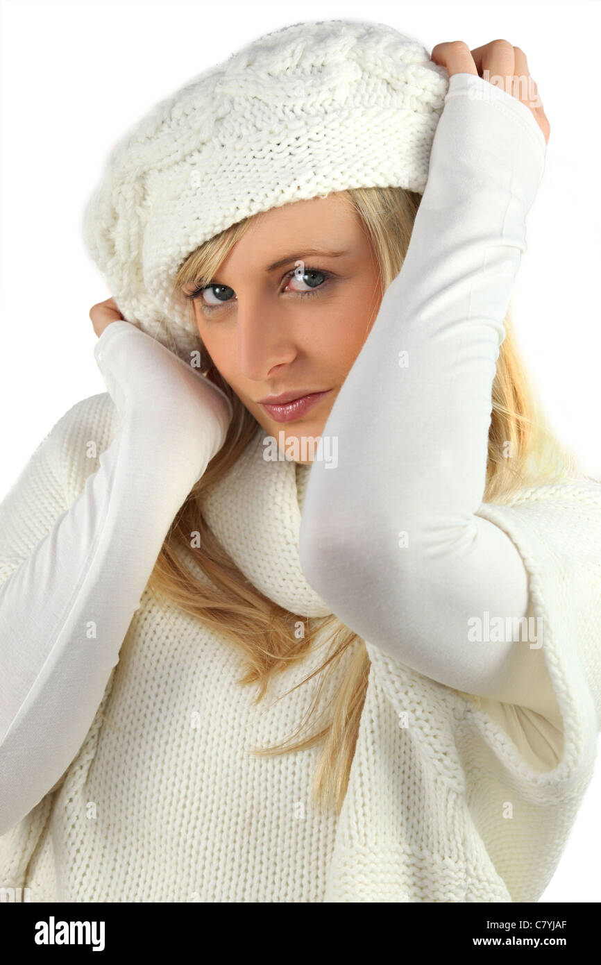 pretty coquettish young blonde wearing white cardigan and bonnet - Stock Image