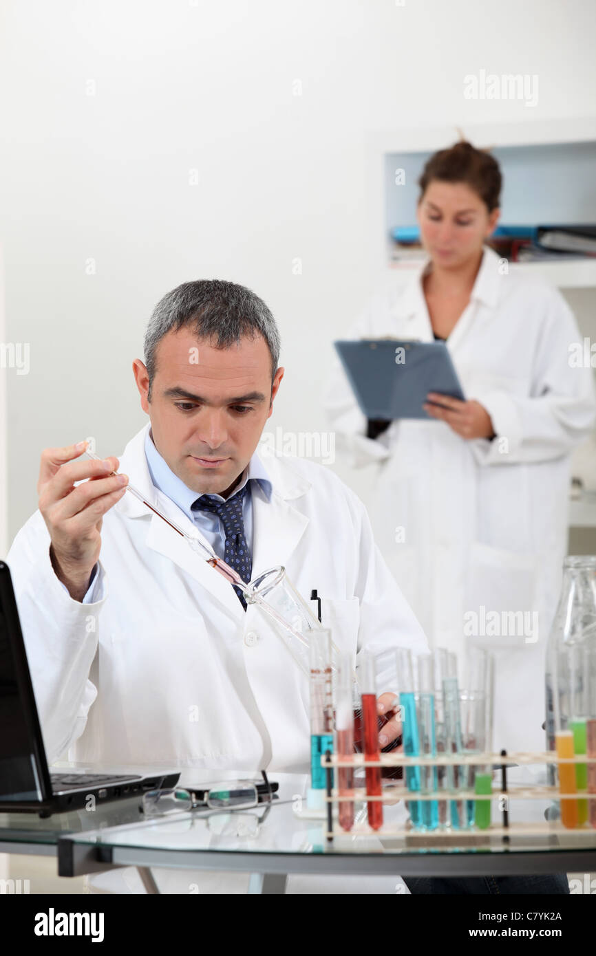 a scientist using test tubes - Stock Image