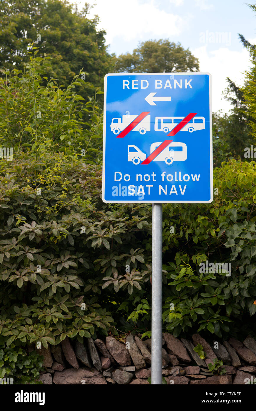 A Road sign in a rural village waring large vehicles not to follow Sat Nav instructions to use an unsuitable country - Stock Image