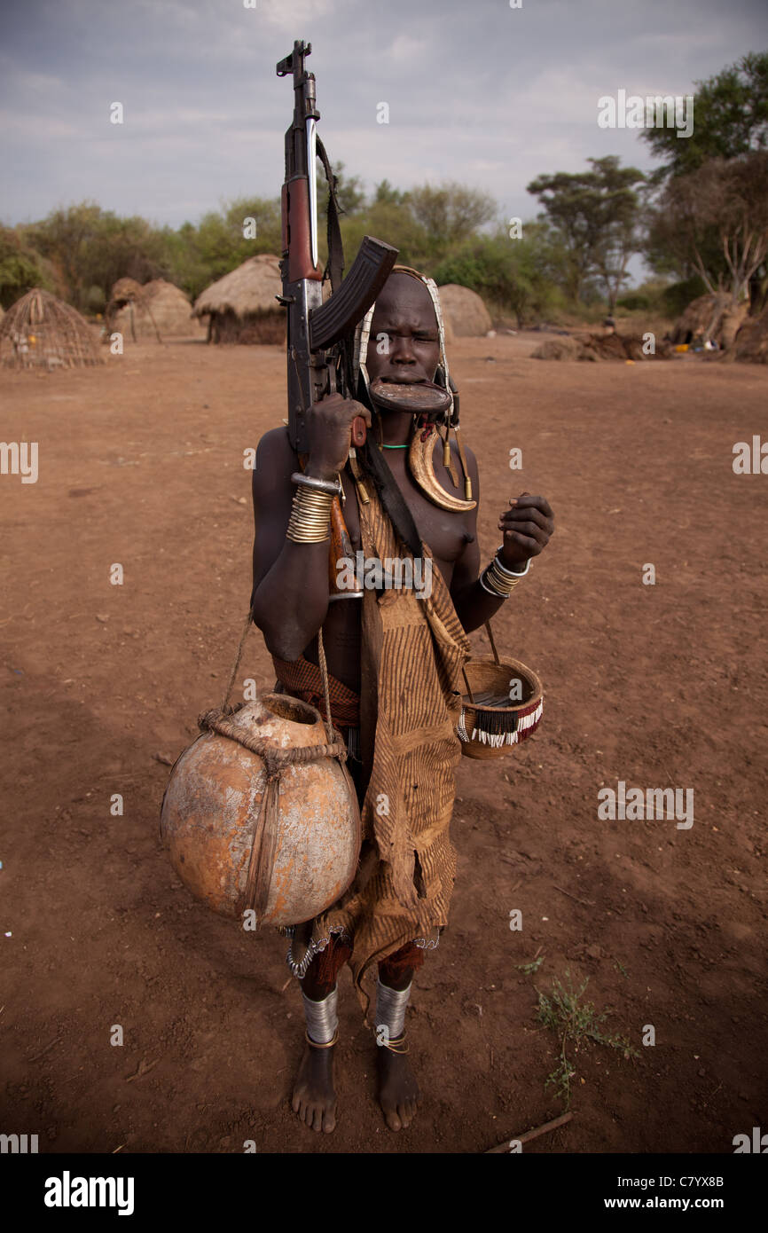 Mursi woman with lip disk and AK47, Jinka, Omo Valley, Ethiopia, Africa - Stock Image