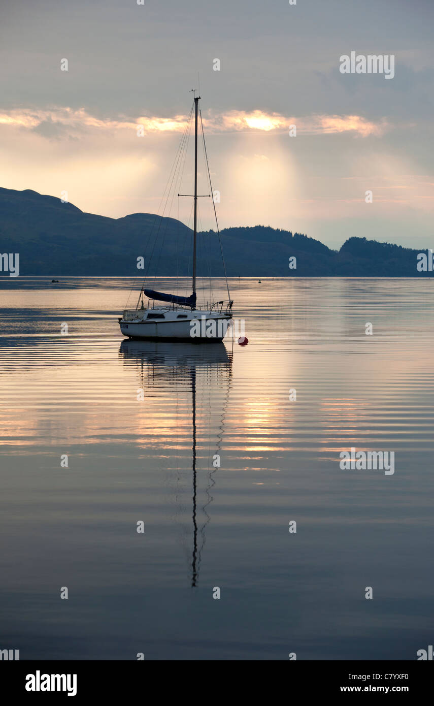 A sailing yacht moored in Loch Lomond, Scotland as the sun rises. - Stock Image
