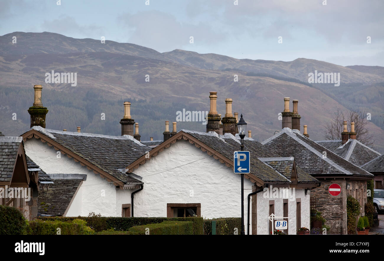 A row of cottages in the Scottish village of Luss on Loch Lomond against the backdrop of Ben Lomond mountain range. - Stock Image