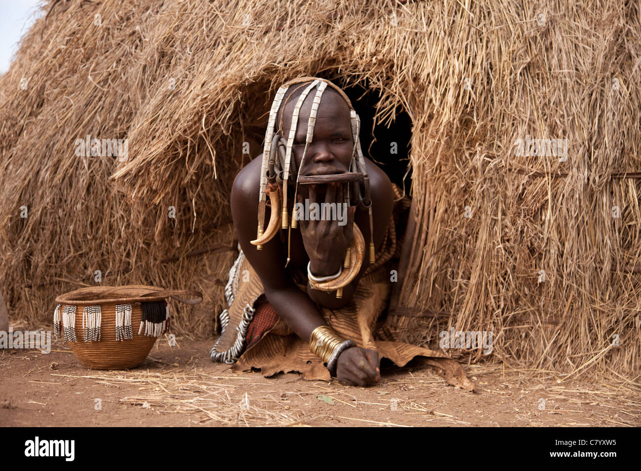 Mursi woman leaving her traditional house, Jinka, Omo Valley, Ethiopia, Africa - Stock Image