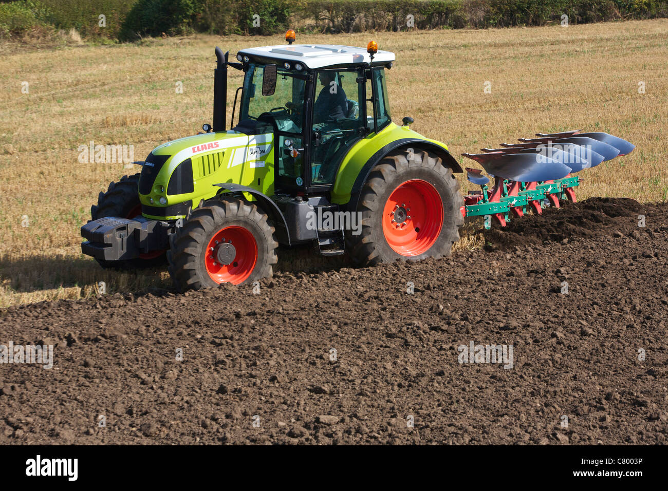 Tractor Ploughing Field Claas ARION 640 - Stock Image