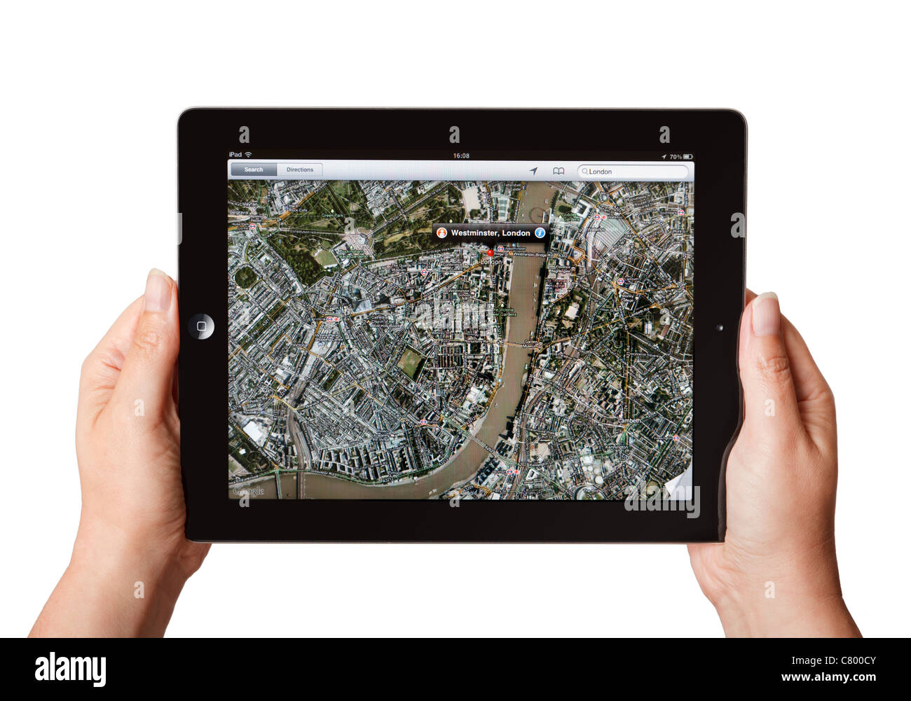 Hands holding iPad showing the Google Maps app centred on London - Stock Image