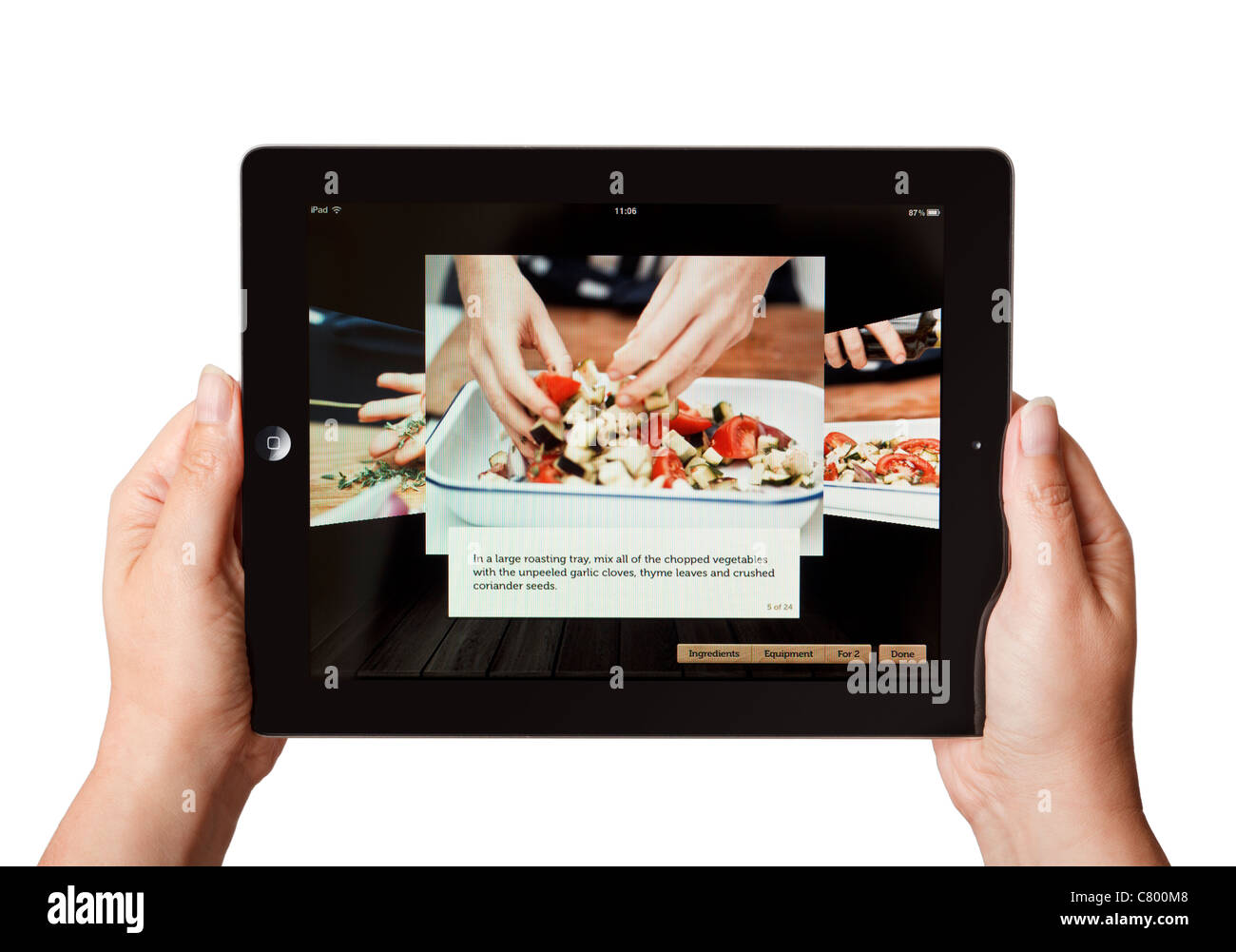 Hands holding an iPad using a cookery app showing how to prepare a meal - Stock Image