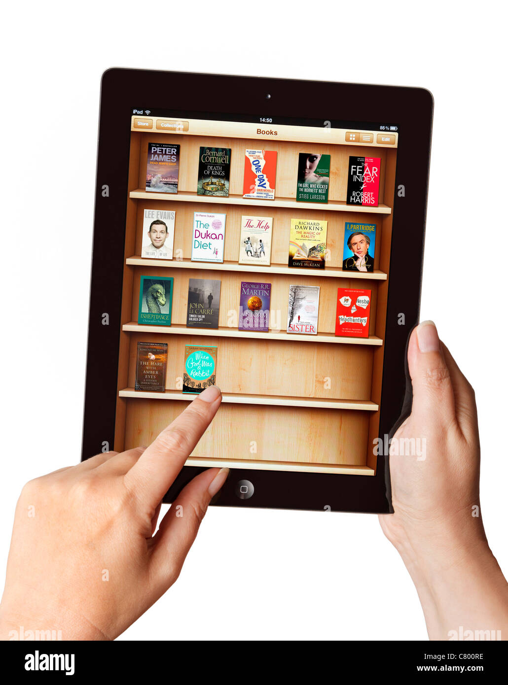 Hands holding iPad and selecting an ebook from the book cover in library app - Stock Image