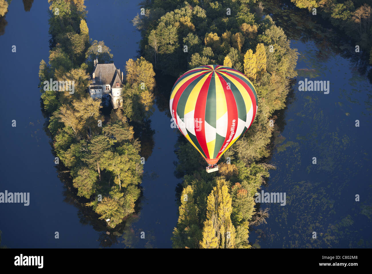 HOT AIR BALLOON DRIFTING OVER TWO SMALL ISLANDS ON THE CHER RIVER (aerial view). Chisseaux, Centre-Val de Loire, - Stock Image