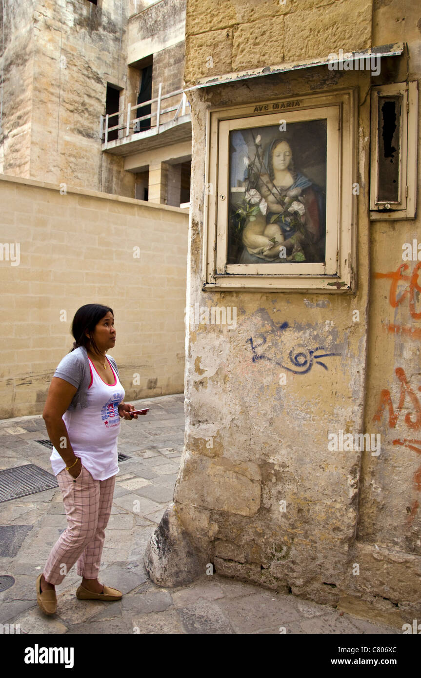 Woman with mobile cell phone looks at an icon of Mary and Christ child - Stock Image