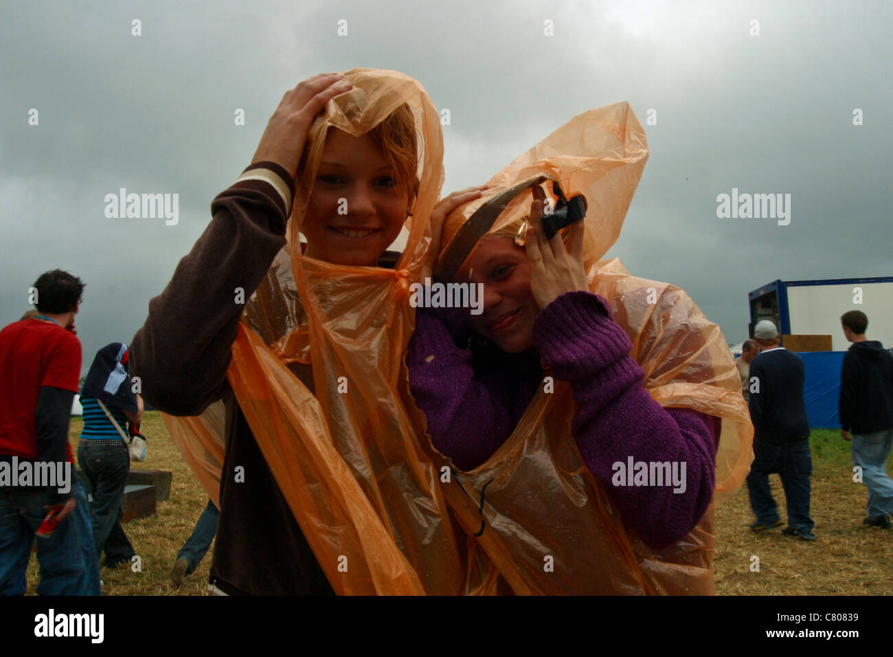 Punters sheltering from the rain at the Glastonbury Festival 2003 - Stock Image