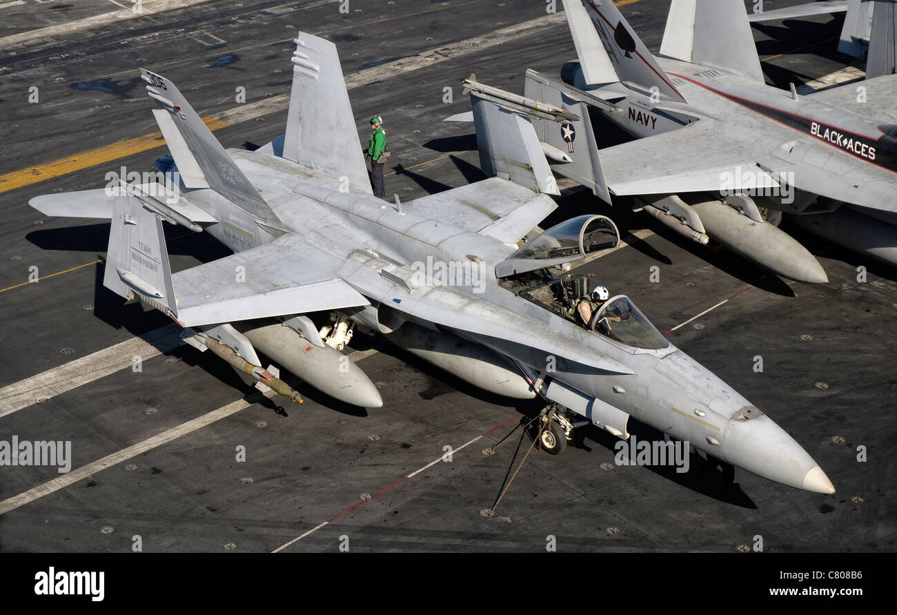 A US Navy F/A-18C Hornet parked on the flight deck of aircraft carrier USS Nimitz. - Stock Image