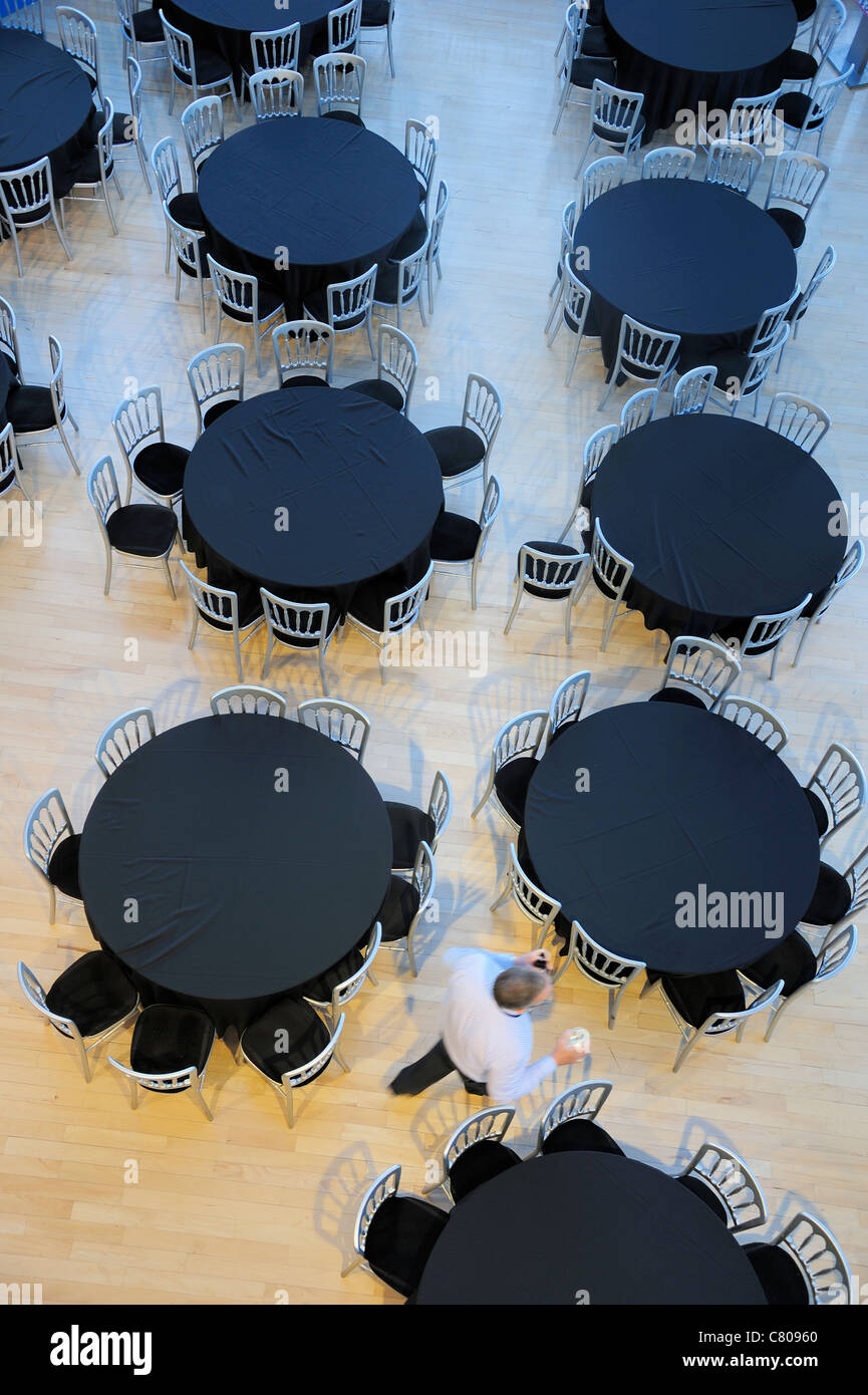Overhead view of a restaurant with empty tables. A waiter passes, motion blur on the man. - Stock Image