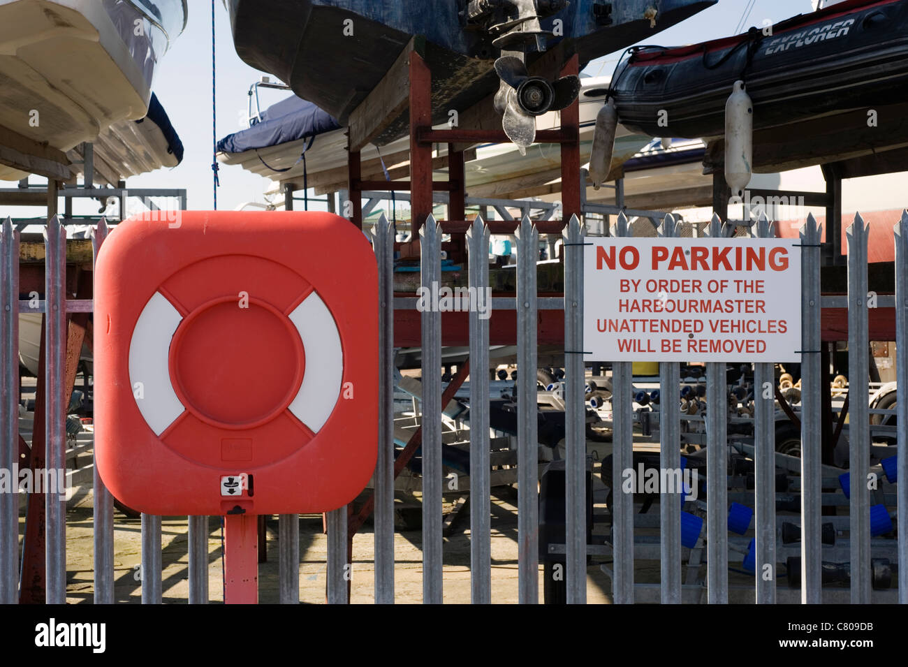 life ring and harbourmaster warning sign on the quayside - Stock Image