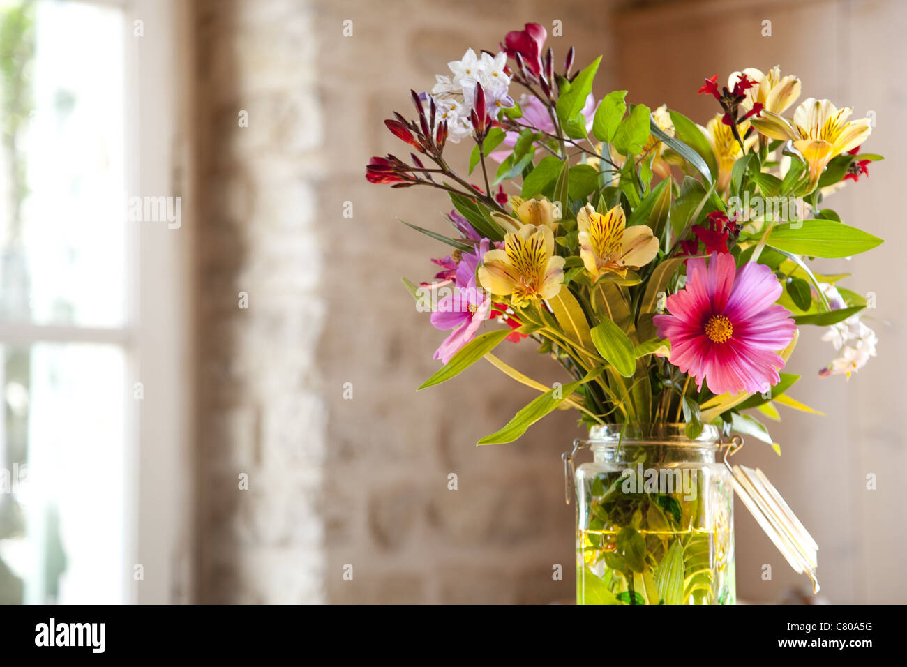 Colour photo of a fresh bouquet of flowers set inside on the kitchen table on a spring morning in France. - Stock Image