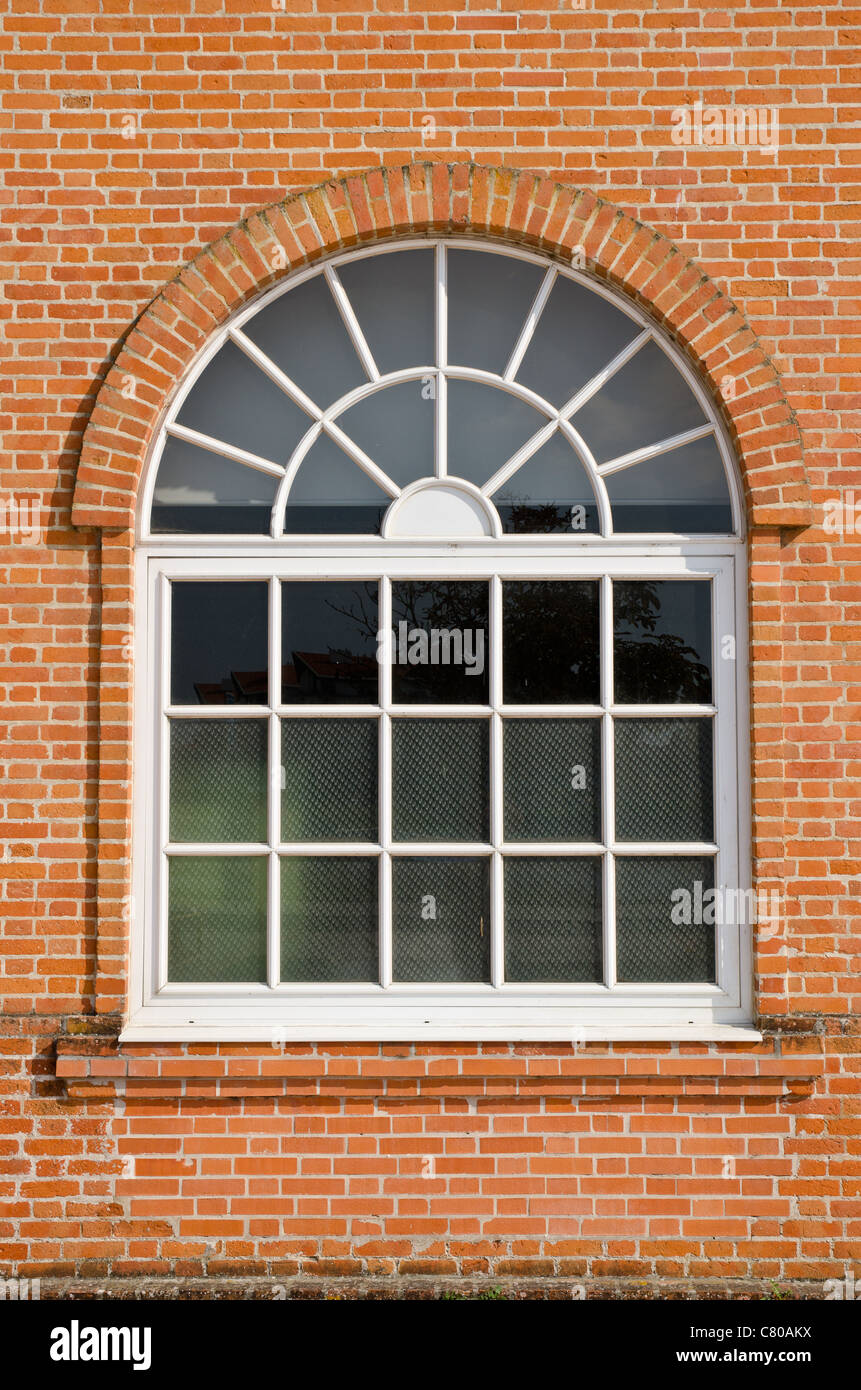 white painted wood arched window in a red brick wall stock photo