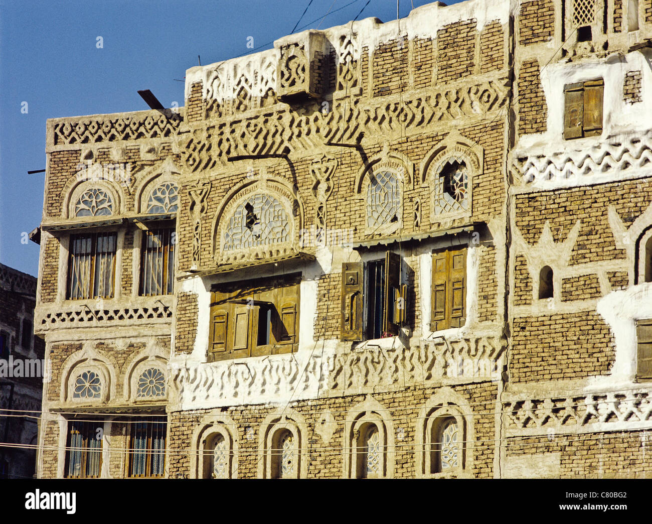 Architectural detail showing tracery windows of a multistory dwelling in the Old City of Sana'a, Yemen Stock Photo