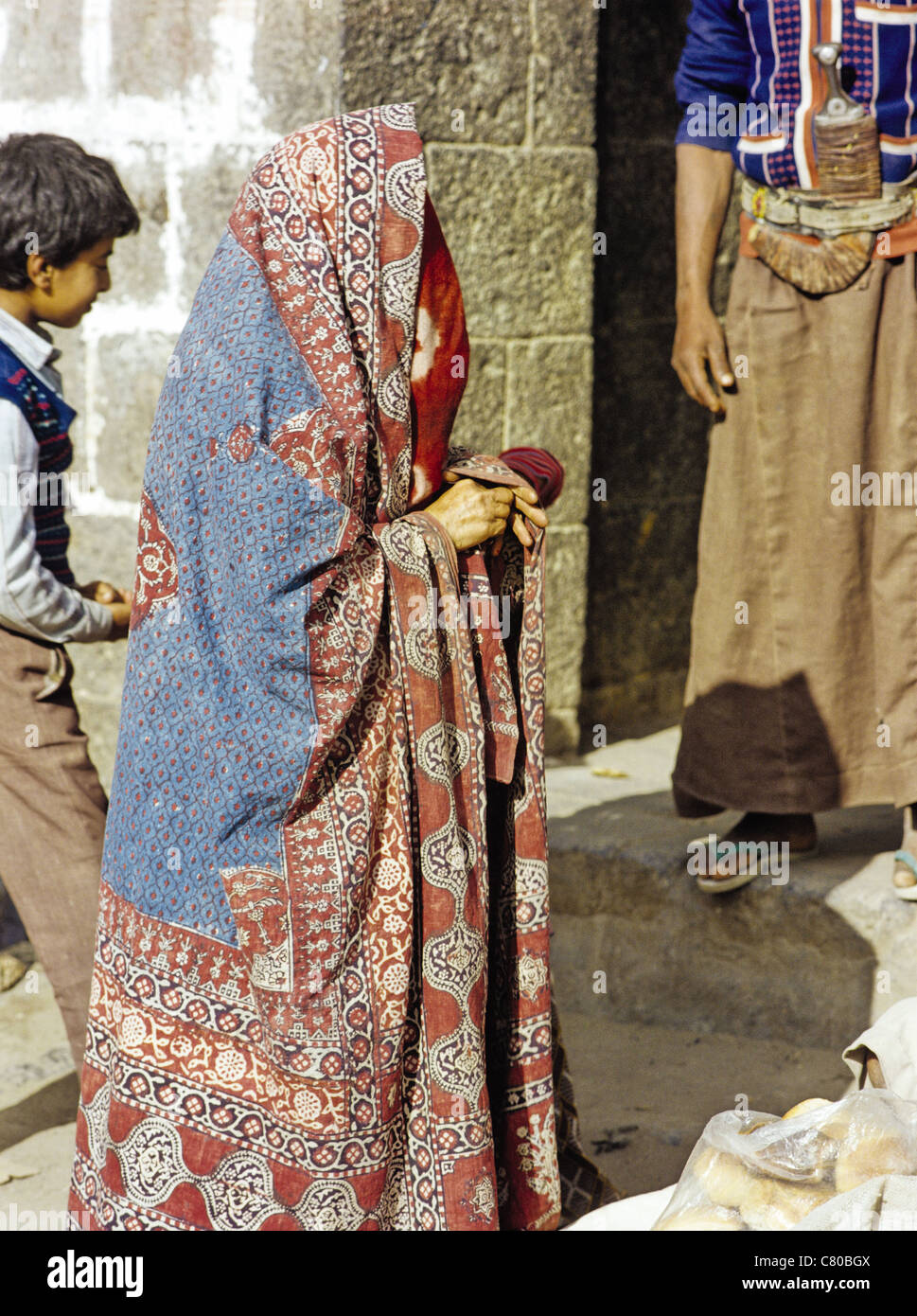 Veiled woman wearing an abaya in the Old City of Sana'a, Yemen - Stock Image