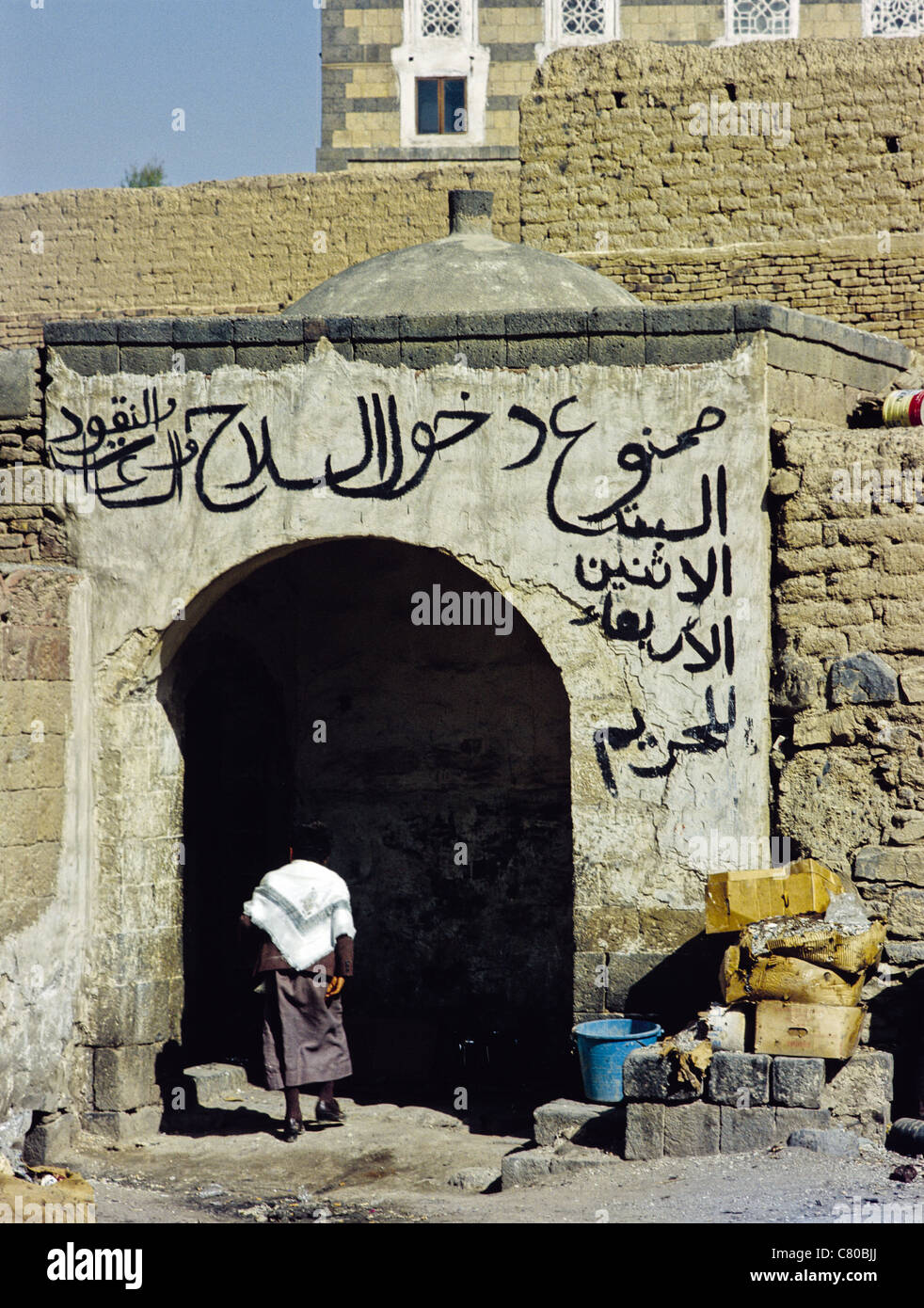 Child entering a building with Arabic calligraphy over the doorway in the Old City of Sana'a, Yemen - Stock Image