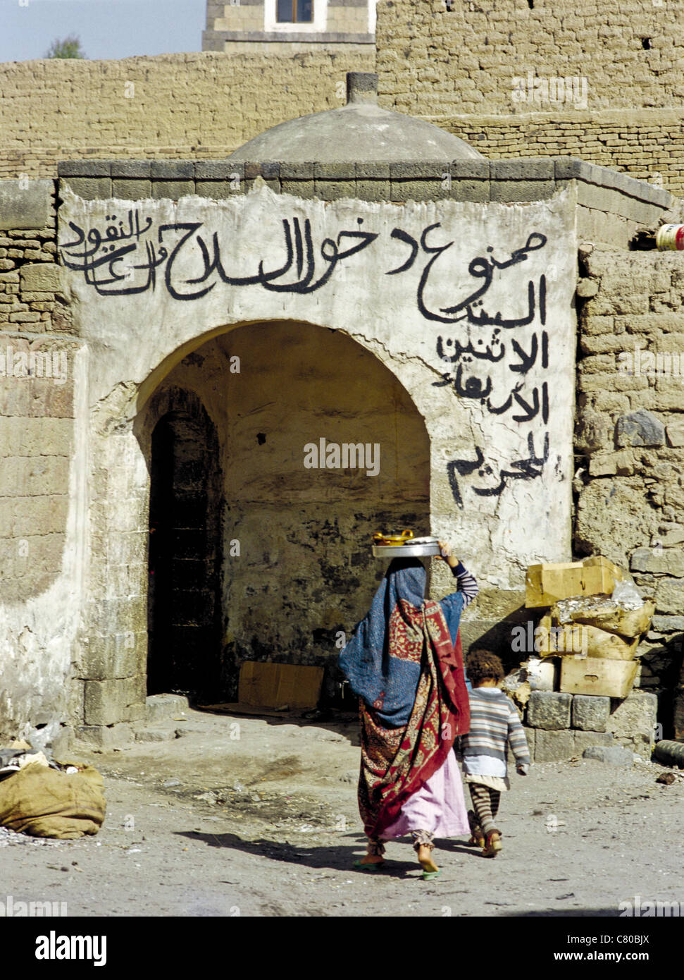 Yemeni woman and child entering a building with Arabic writing over the doorway in the Old City of Sana'a, Yemen - Stock Image