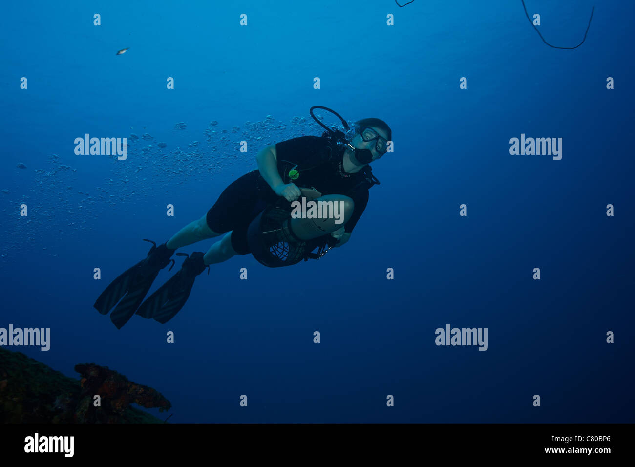 Scuba diver uses a diver propulsion vehicle to navigate the waters off the coast of Bonaire, Caribbean Netherlands. - Stock Image