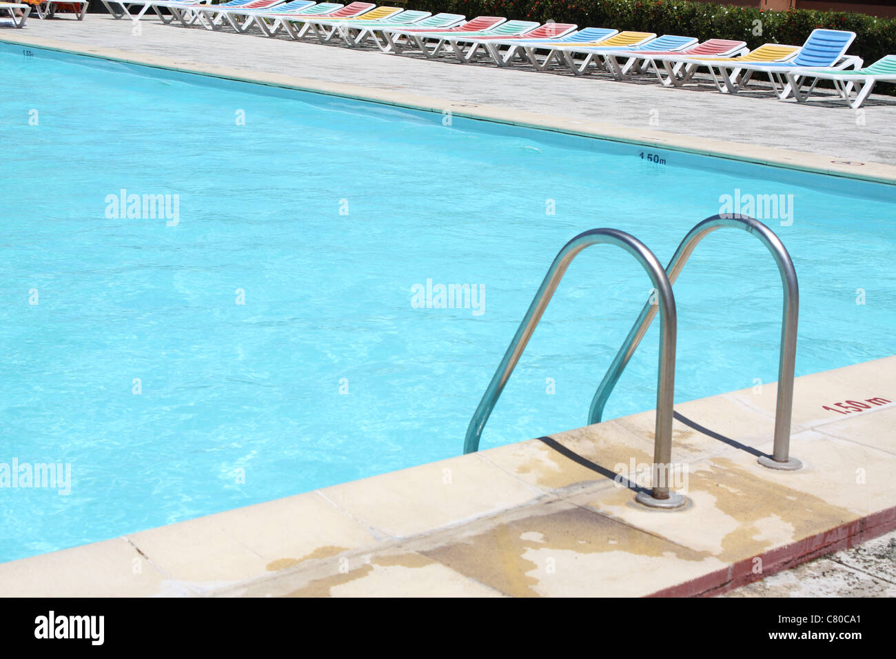 Handrail steps leading into a swimming pool - Stock Image