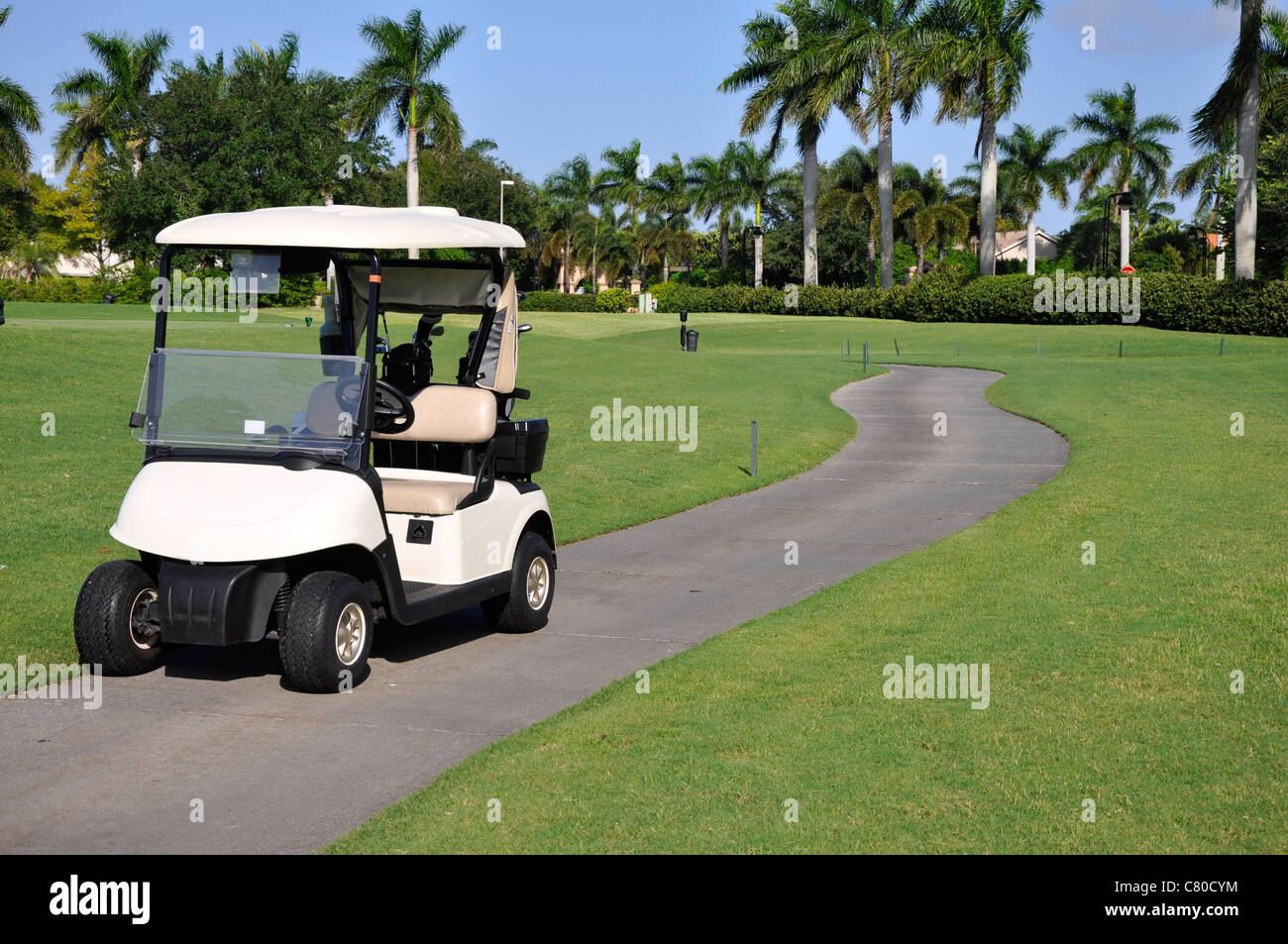Empty golf cart sitting on a macadam path by a golf course - Stock Image