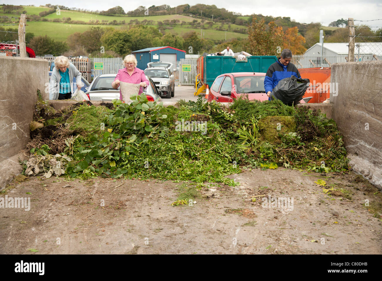 People dumping sacks of green garden waste at a recycling centre UK - Stock Image