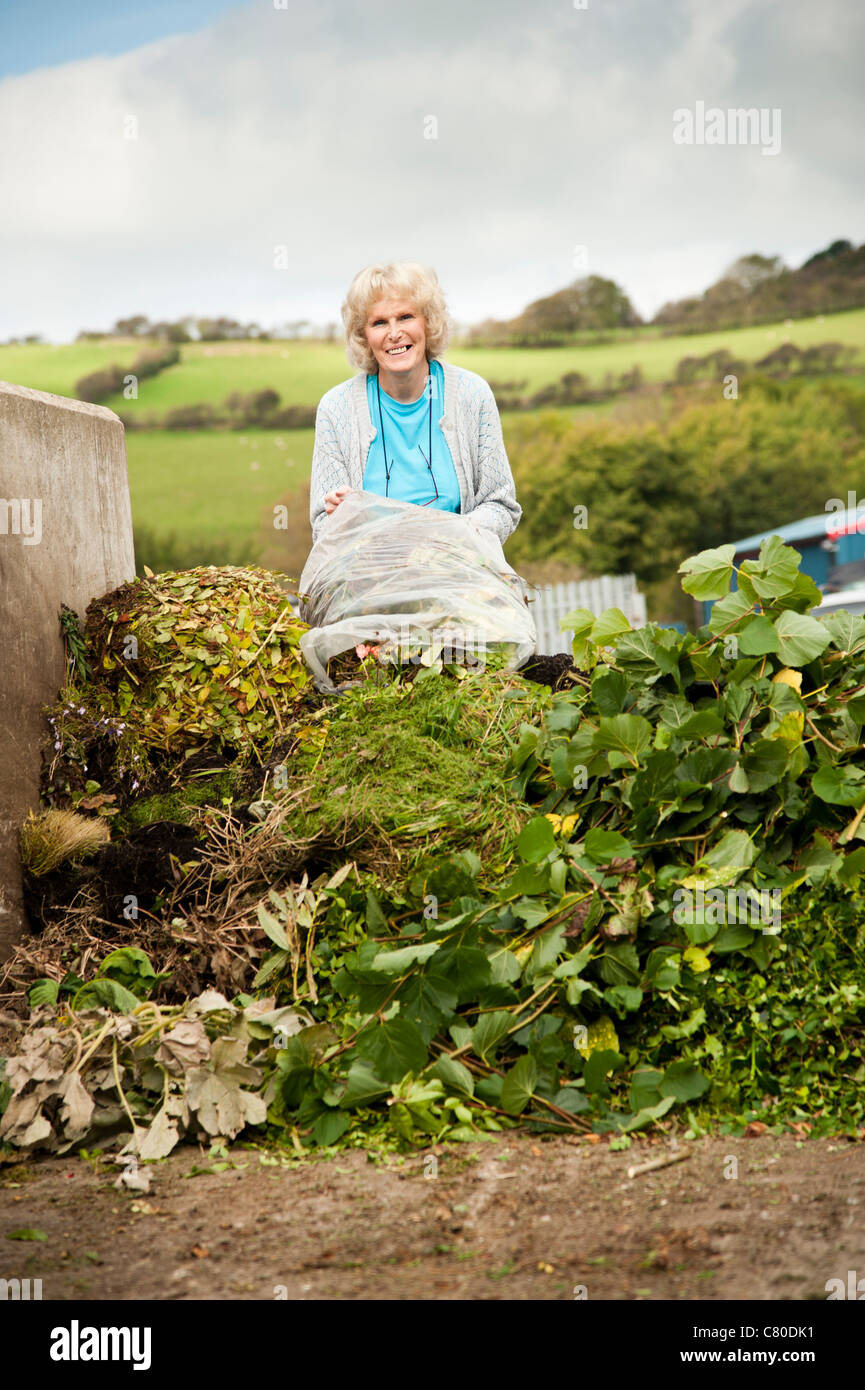a woman dumping sacks of green garden waste at a recycling centre UK - Stock Image
