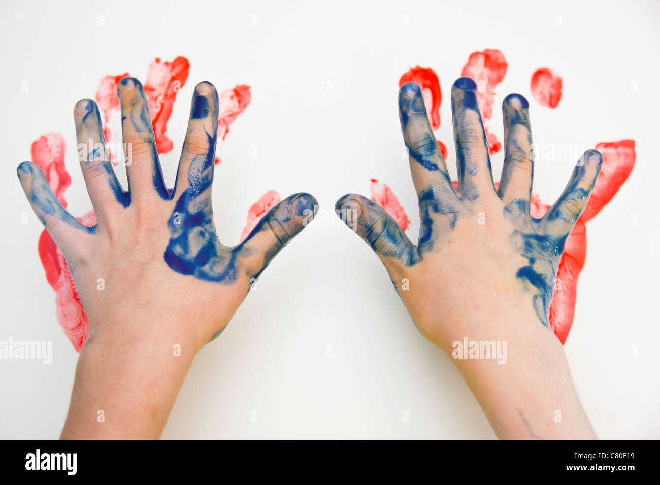 A child painting with his hands and fingers - Stock Image