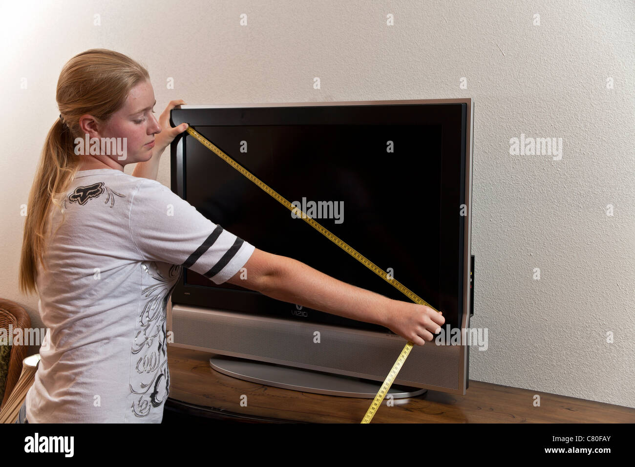 Teenage girl measures the dimensions of an 80 centimeter TV Screen. MR © Myrleen Pearson - Stock Image