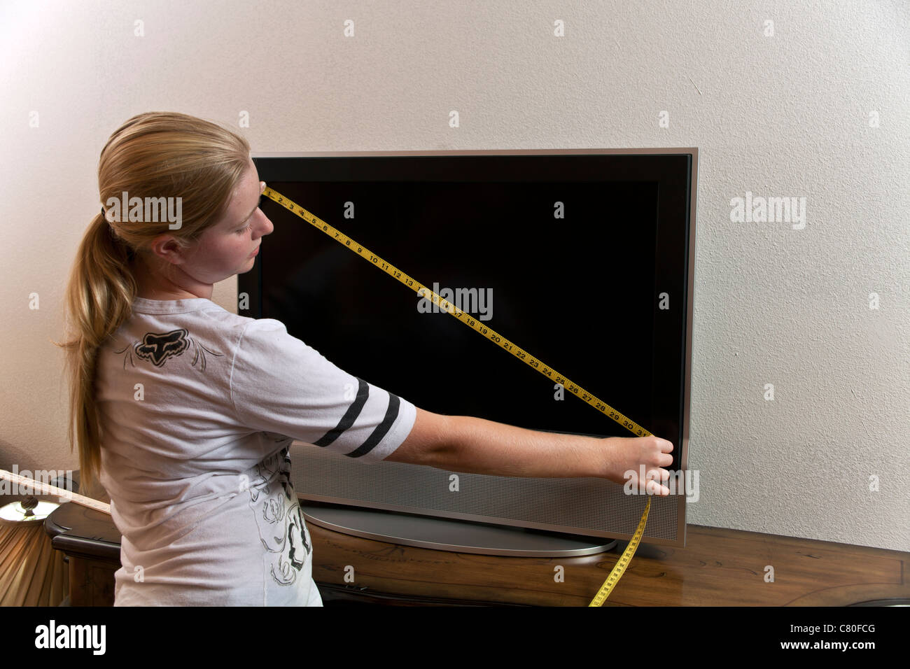 Teenage Girl Measures The Dimensions Of A 32 Inch Tv Screen Mr