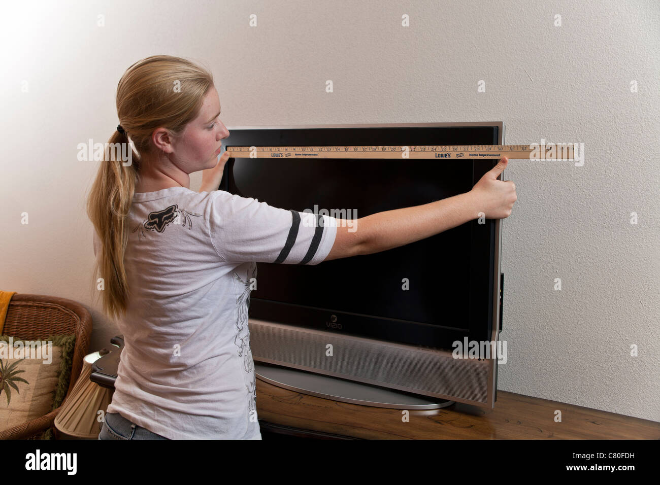 Teenage girl measures the dimensions of a 32 inch TV Screen. MR © Myrleen Pearson - Stock Image