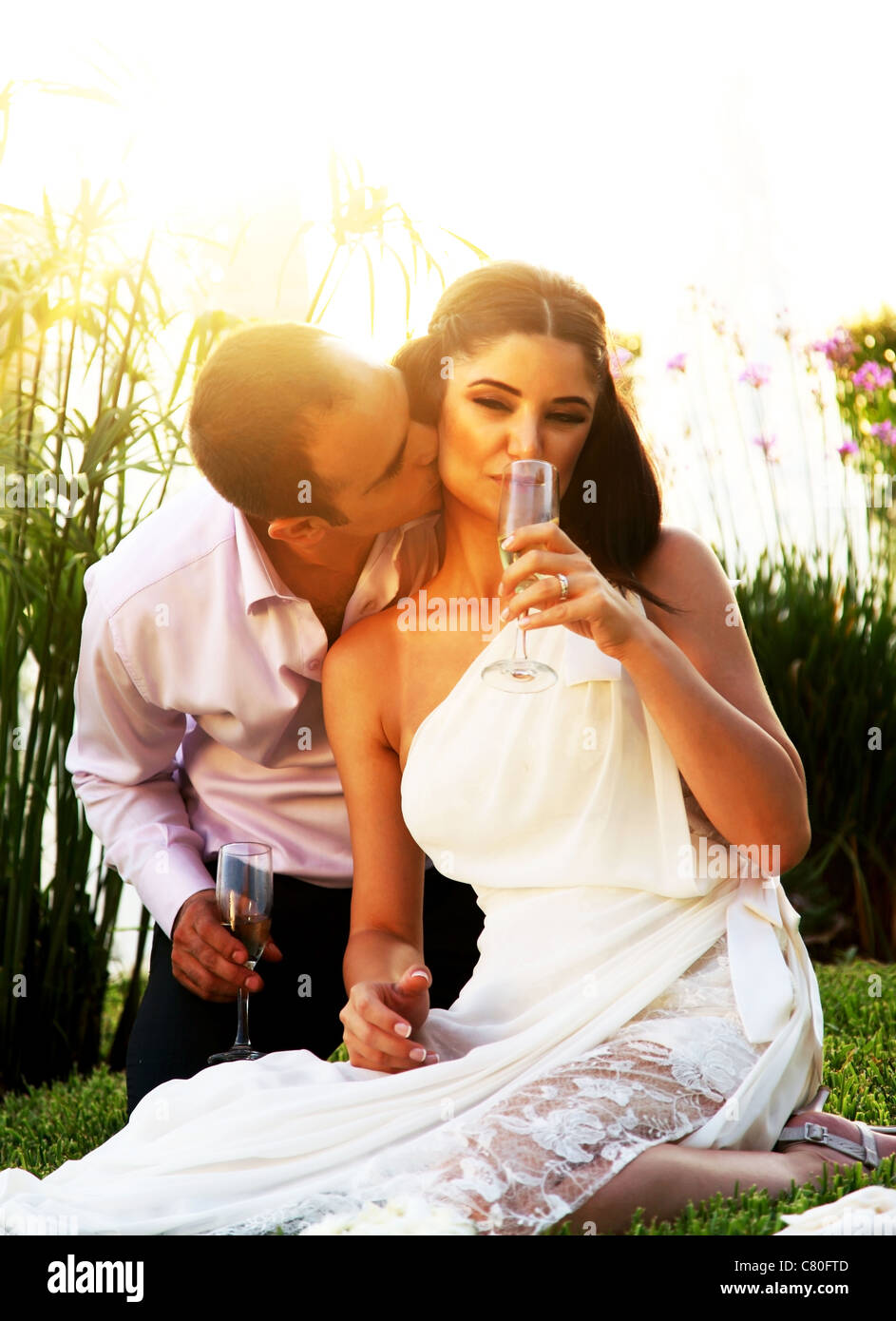 Happy young couple kissing outdoors, wedding day - Stock Image