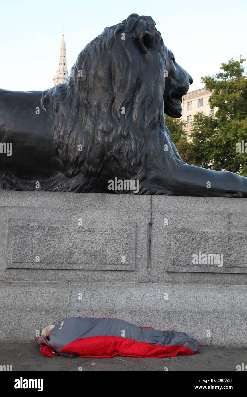 Homeless sleeper underneath one of the lions at Trafalgar Square, London - Stock Image