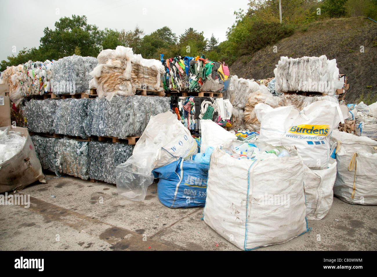 Bales of compacted waste awaiting collection at a  recycling centre UK - Stock Image