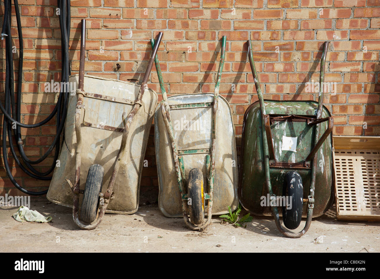 Three wheelbarrows leaning against a brick wall in a farmyard - Stock Image