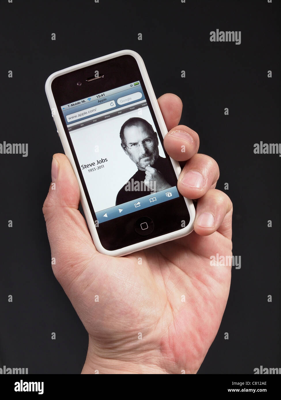 Apple homepage with Steve Jobs in memoriam on the day he died, shown on an iPhone 4 in hand. - Stock Image