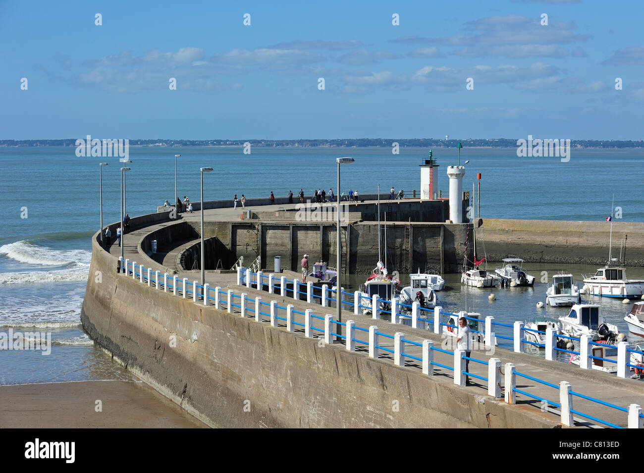 Harbour with anglers fishing from seawall at Saint-Michel-Chef-Chef, Loire-Atlantique, France Stock Photo