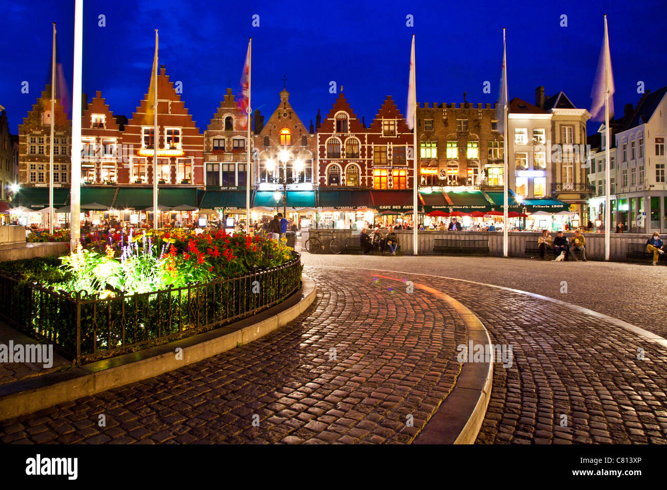 Bars, cafes, restaurants, and tourists in the Grote Markt or Market Square in Bruges, (Brugge), Belgium at twilight. Stock Photo