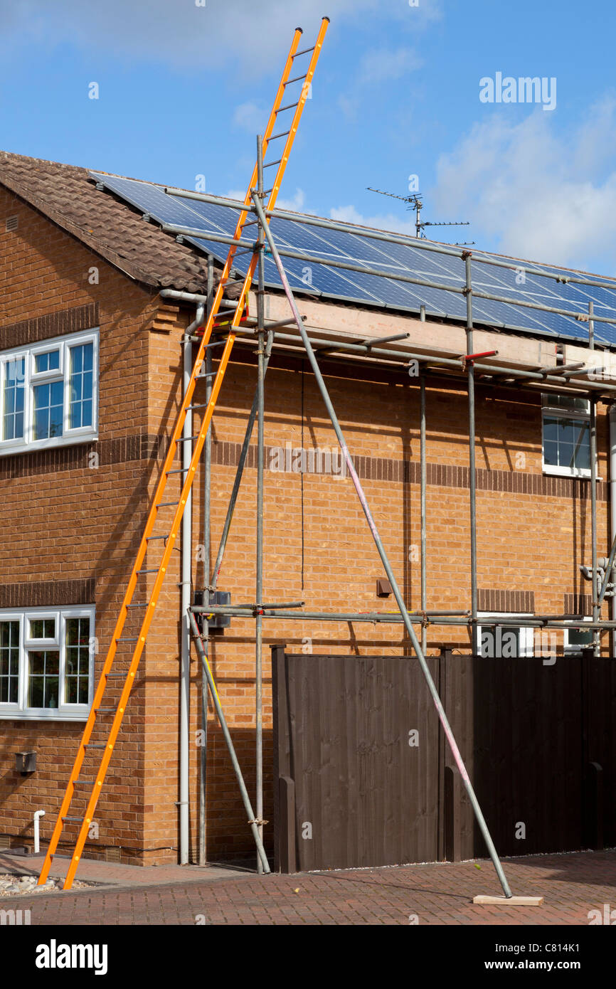 solar panels being fitted on a detached house roof england uk gb eu europe - Stock Image