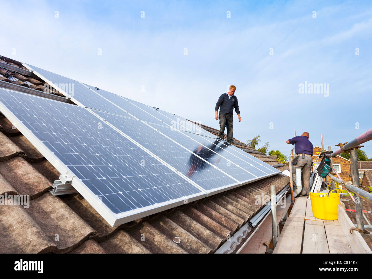 fitting solar panels on detached house roof england uk gb eu europe - Stock Image