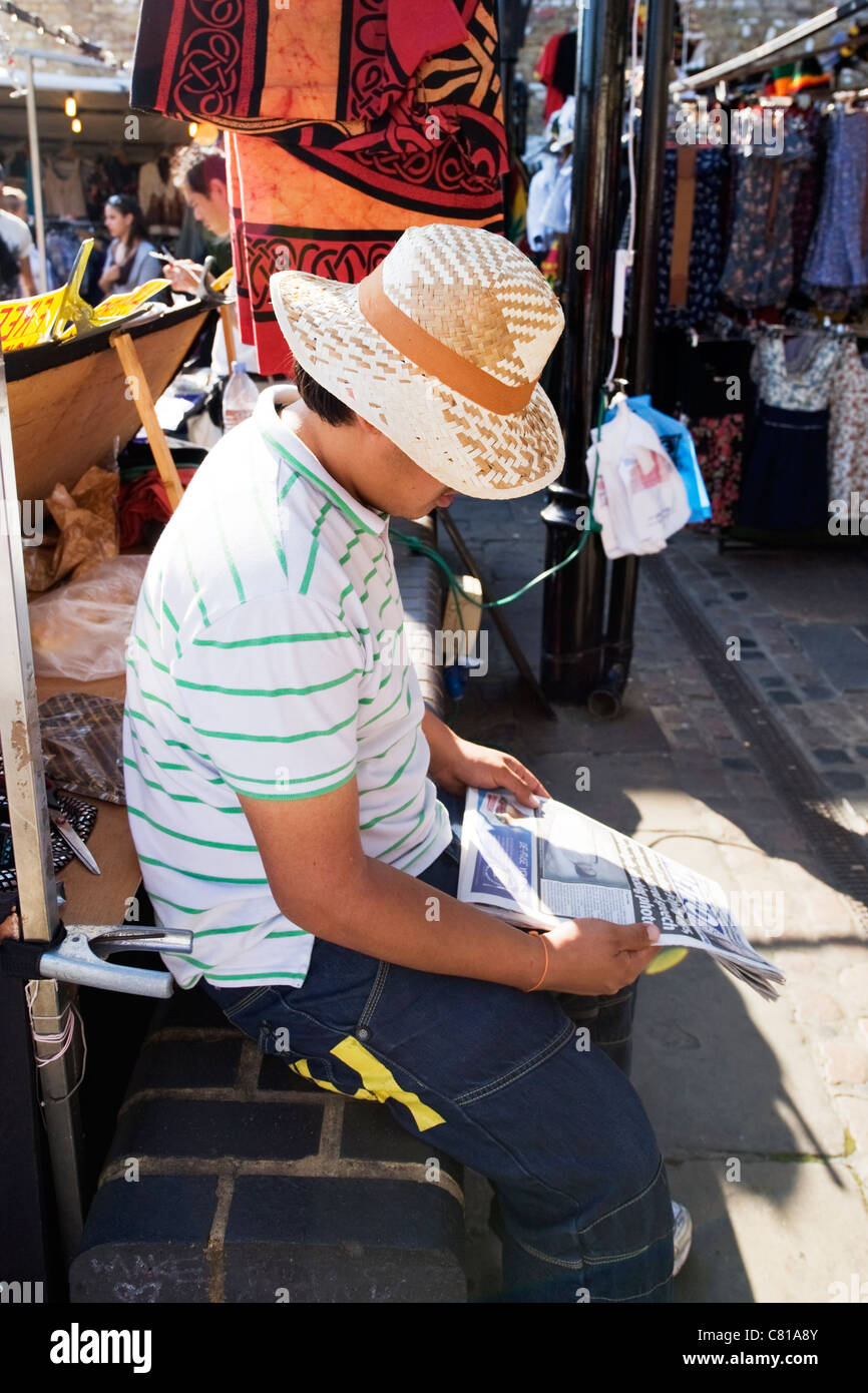 London Camden Town Lock Stables market stall holder Asian young man male straw hat reading Metro newspaper waiting - Stock Image