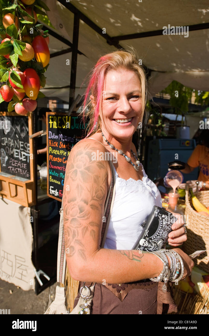 London Camden Town Lock Stables market smiling pretty young blond & pink haired woman lady female tattoos Stock Photo