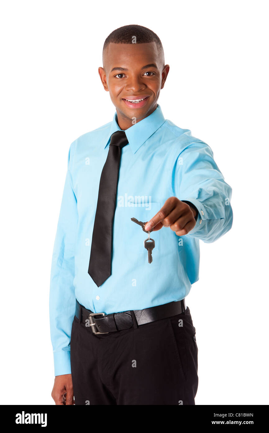 Happy corporate business man realtor handing over keys to new house, dressed in blue shirt and black tie, isolated. Stock Photo
